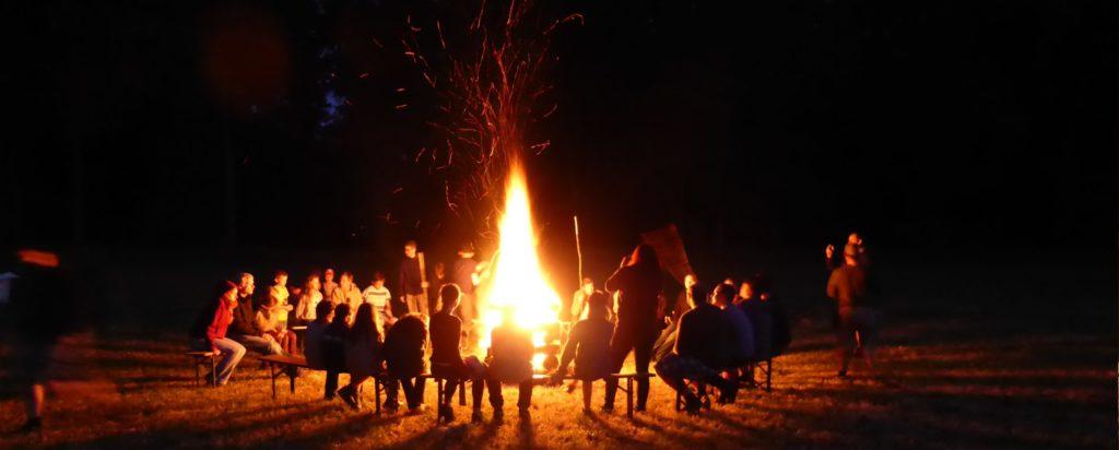 Pfadfinder im Sommerlager sitzen um Lagerfeuer. Nachtaufnahme eines Ferienlagers in den Sommerferien der Pfadfinder im Stamm DPSG Christus König aus Duisburg Rheinhausen Bergheim.